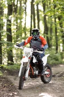 Vooraanzicht stijlvolle man motor rijden in het bos