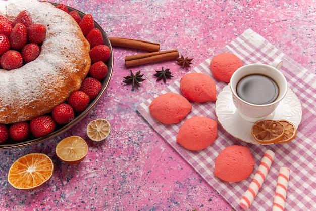 Vooraanzicht suiker poedertaart aardbeientaart met thee en cakes op roze