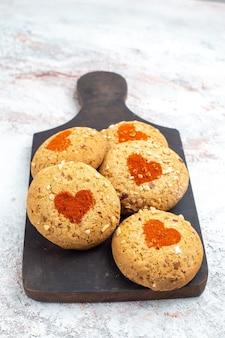 Vooraanzicht suikerkoekjes heerlijke snoepjes voor thee op een witte ondergrond taartkoekjes suikerkoekje zoete koek