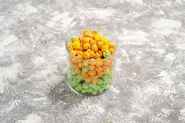 Vooraanzicht suikersuikergoed binnen glas op witte ruimte
