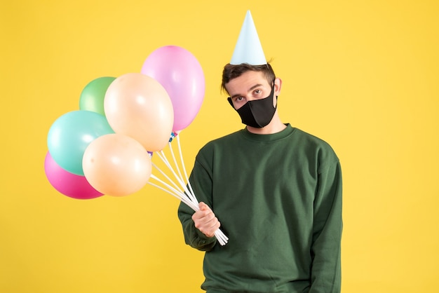 Vooraanzicht teleurgestelde jongeman met feestmuts en kleurrijke ballonnen staande op geel