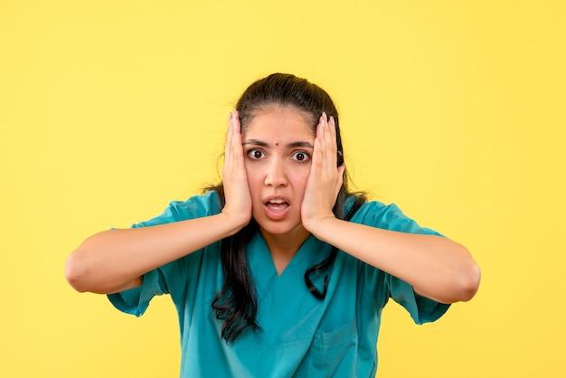 Vooraanzicht teleurgestelde vrouwelijke arts in uniform staande op gele geïsoleerde achtergrond