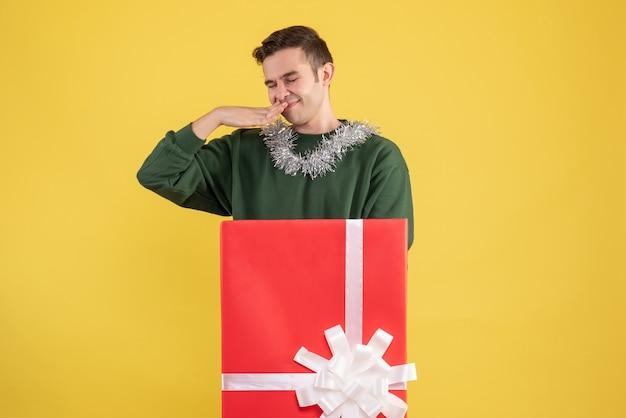 Vooraanzicht tevreden jonge man die achter grote geschenkdoos op geel