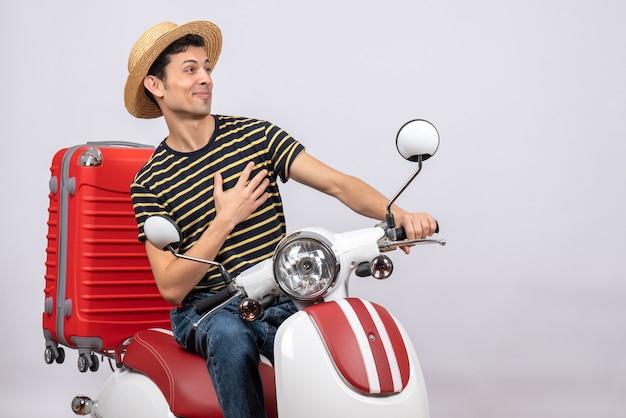 Vooraanzicht tevreden jongeman met strooien hoed op bromfiets hand op zijn borst zetten