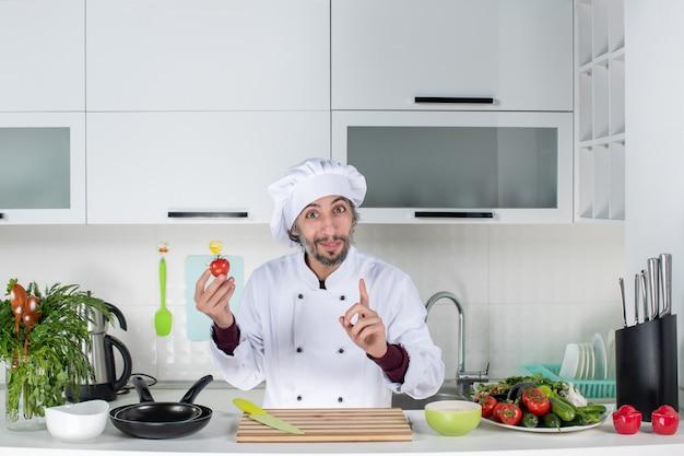 Vooraanzicht tevreden mannelijke chef-kok in uniform die tomaat in de keuken vasthoudt