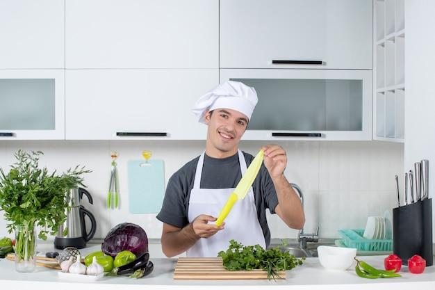 Vooraanzicht tevreden mannelijke chef-kok in uniform met mes in de keuken