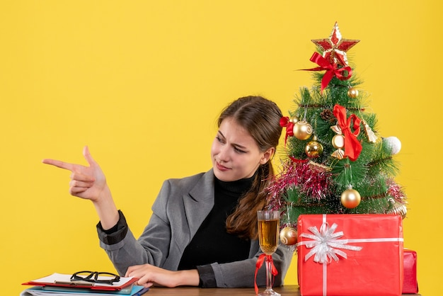 Vooraanzicht tevreden meisje zittend aan de tafel wijzend met vinger iets in de buurt van kerstboom en geschenken cocktail