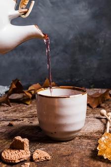 Vooraanzicht thee wordt gegoten in beker
