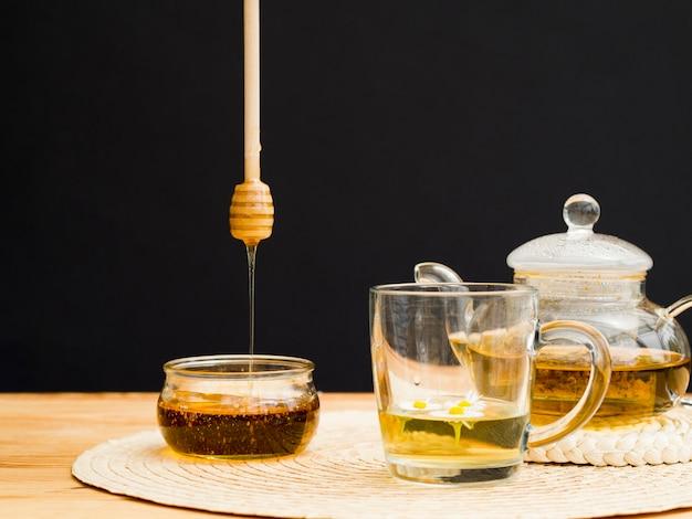 Vooraanzicht theepot met glas en honing