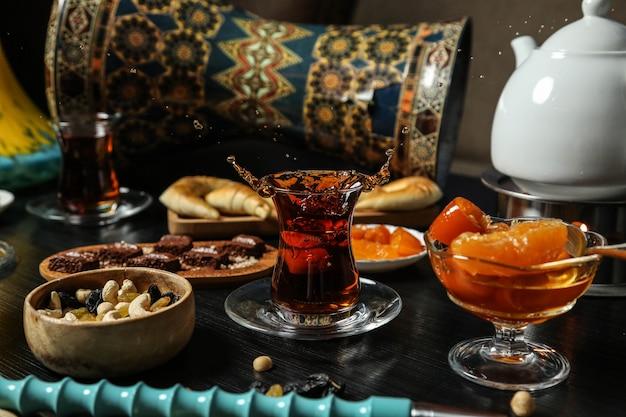 Vooraanzicht theeservies thee in een armudu glas met jam snoep, noten met rozijnen en een reep chocola op tafel