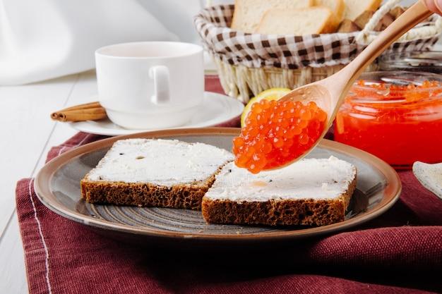 Vooraanzicht toast met boter en een lepel van rode kaviaar op een bord met een kopje thee