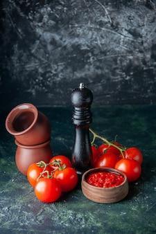 Vooraanzicht tomatensaus met rode tomaten op het donkere oppervlak tomaat rode kleur kruiden peper zout