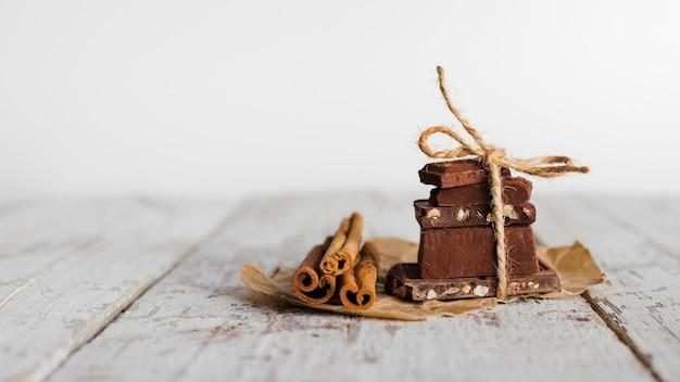 Vooraanzicht toren van chocolade snoepjes en kaneelstokjes op papieren zak