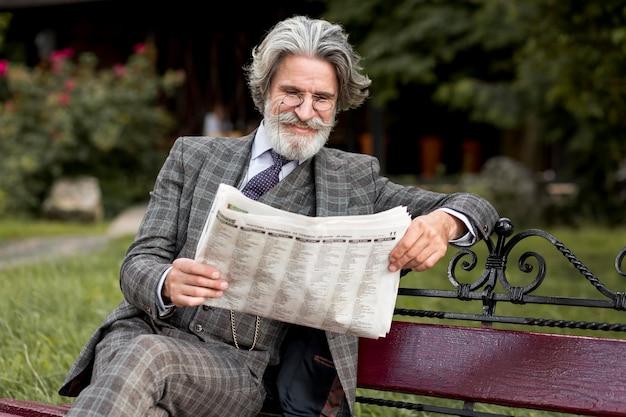 Vooraanzicht trendy volwassen man krant lezen