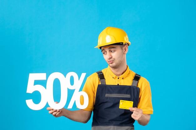 Vooraanzicht triest mannelijke werknemer in uniform met schrijven en creditcard op blauw