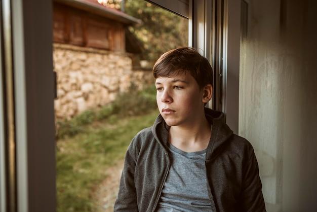 Vooraanzicht trieste jongen naar buiten kijken