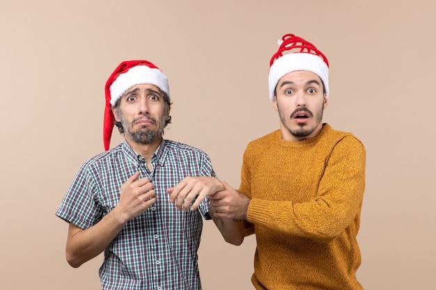 Vooraanzicht twee depressieve jongens met kerstmutsen op beige geïsoleerde achtergrond