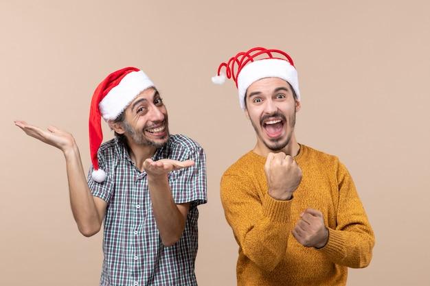 Vooraanzicht twee gelukkige jongens met kerstmutsen waarvan één met open handen en de andere stoten op beige geïsoleerde achtergrond