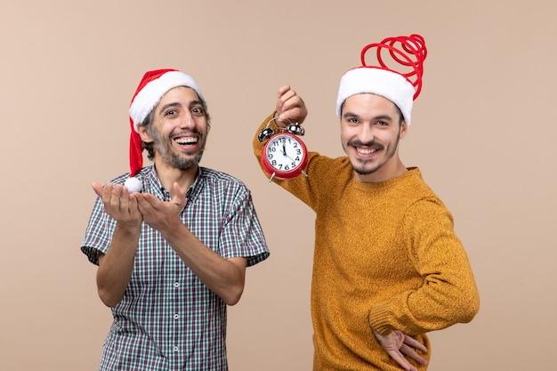 Vooraanzicht twee gelukkige mannen die een wekker houden en op beige geïsoleerde achtergrond glimlachen