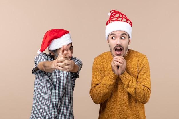 Vooraanzicht twee grappige jongens met kerstmutsen een vinger pistool teken maken en de andere bang op beige geïsoleerde achtergrond