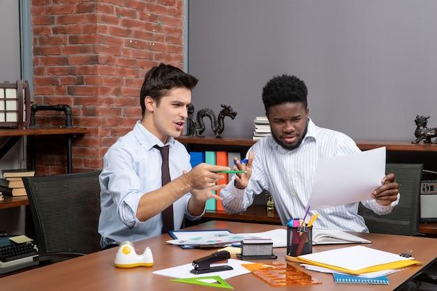 Vooraanzicht twee hardwerkende zakenlieden die bevredigend samenwerken