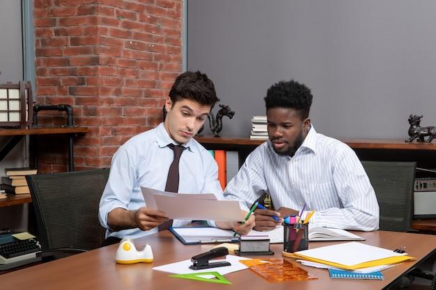 Vooraanzicht twee hardwerkende zakenlieden die project op het werk bespreken