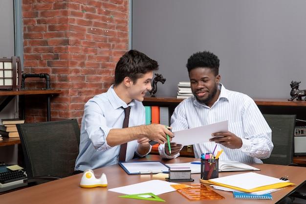 Vooraanzicht twee hardwerkende zakenlieden die project op kantoor bespreken