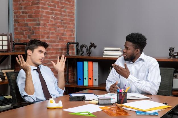 Vooraanzicht twee hardwerkende zakenlieden in formele kleding aan tafel zitten met kantoorspullen