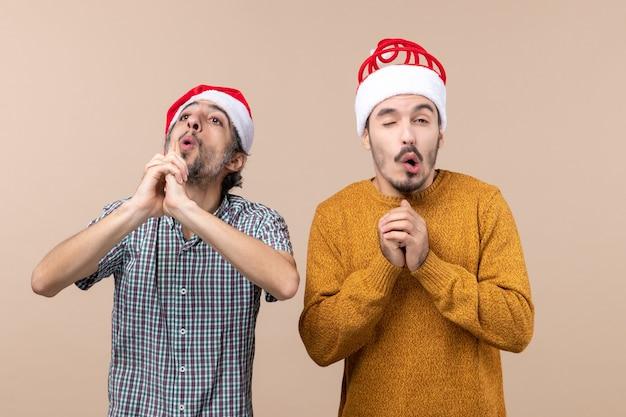Vooraanzicht twee jongens met santahoeden die vingerpistoolteken maken en andere bang op beige geïsoleerde achtergrond maken