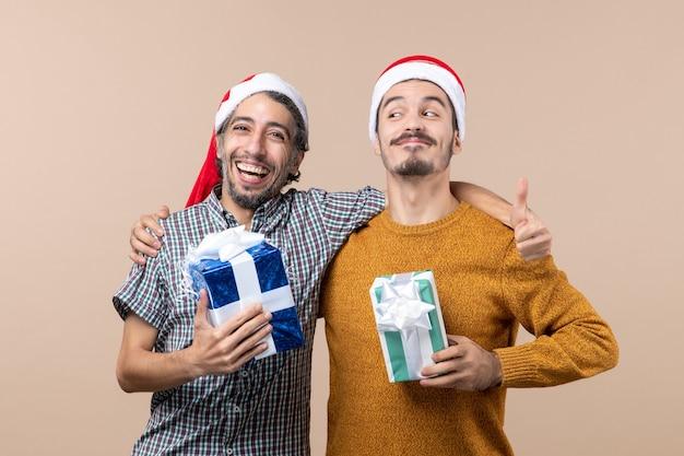 Vooraanzicht twee lachende jongens knuffelen en houden kerstcadeautjes op beige geïsoleerde achtergrond