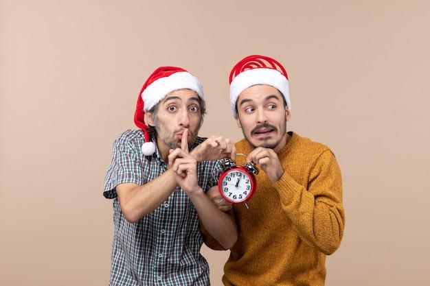Vooraanzicht twee mannen die allebei rode klok één houden die shh teken op beige geïsoleerde achtergrond maken
