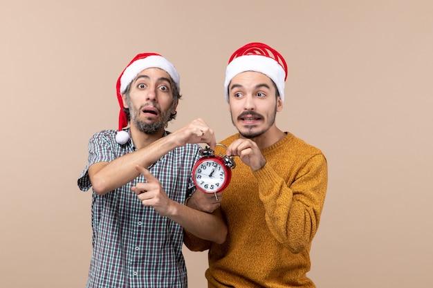 Vooraanzicht twee mannen die allebei rode klok op beige geïsoleerde achtergrond houden