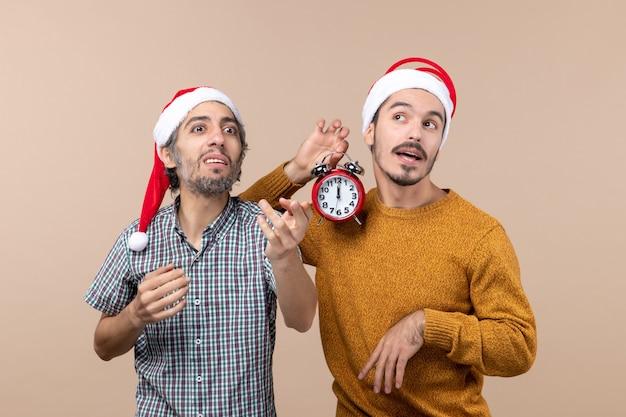 Vooraanzicht twee mannen die iemand bellen en de andere met een wekker op beige geïsoleerde achtergrond