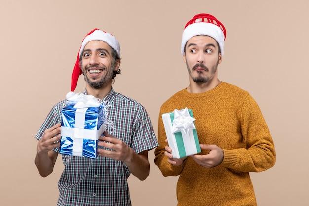 Vooraanzicht twee mannen een blij en verward santa hoeden dragen op beige geïsoleerde achtergrond