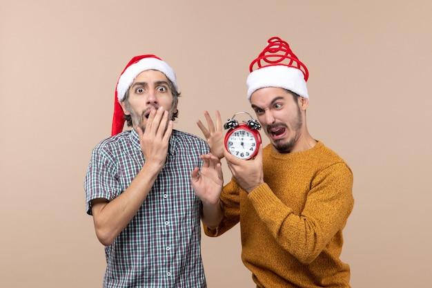 Vooraanzicht twee mannen een boos op de wekker en de andere verrassend op beige geïsoleerde achtergrond