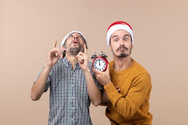 Vooraanzicht twee mannen een met een wekker en de andere kijken naar plafond op beige geïsoleerde achtergrond