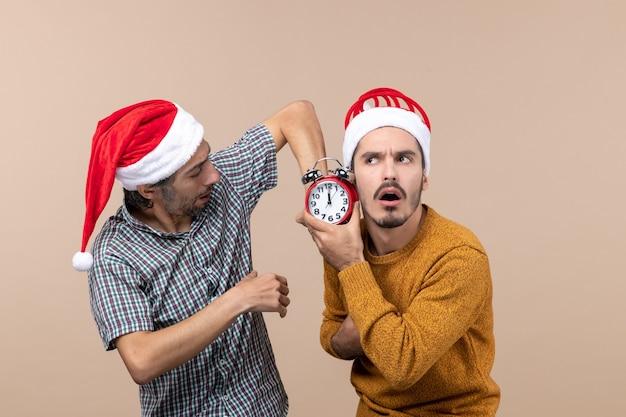 Vooraanzicht twee mannen een met een wekker op beige geïsoleerde achtergrond