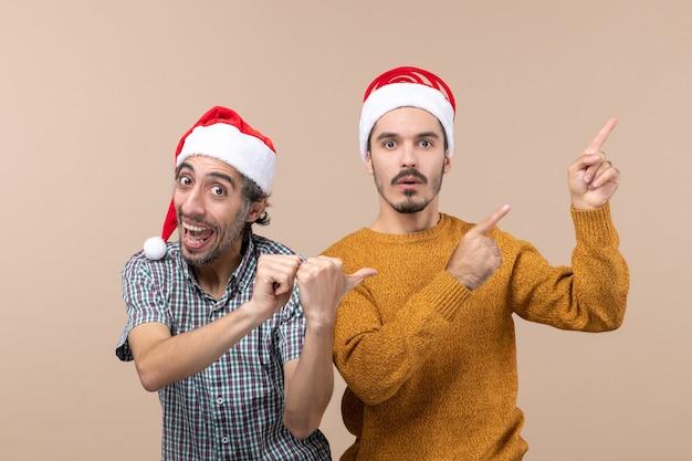 Vooraanzicht twee mannen gelukkig en droevig met santahoeden die beide iets op geïsoleerde achtergrond tonen