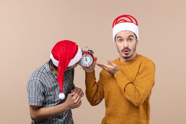 Vooraanzicht twee mannen kijken naar en de andere met een wekker op beige geïsoleerde achtergrond