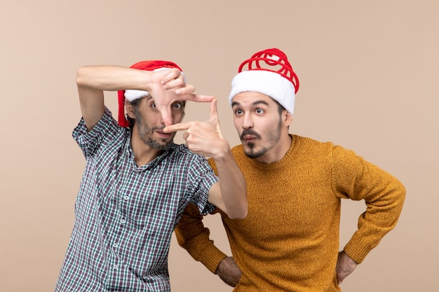 Vooraanzicht twee nieuwsgierige jongens met kerstmutsen een camera ondertekenen met zijn handen op beige geïsoleerde achtergrond