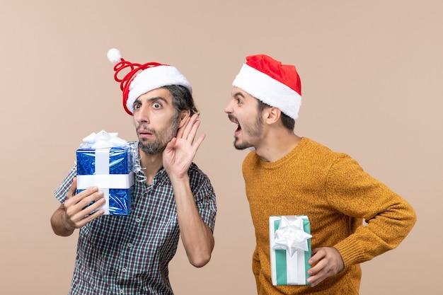 Vooraanzicht twee nieuwsgierige jongens roddelen en houden kerstcadeautjes op beige geïsoleerde achtergrond