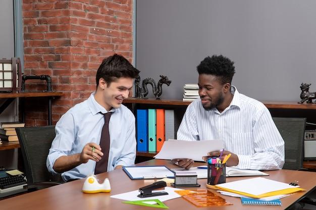 Vooraanzicht twee tevreden zakenlieden die project op het werk bespreken