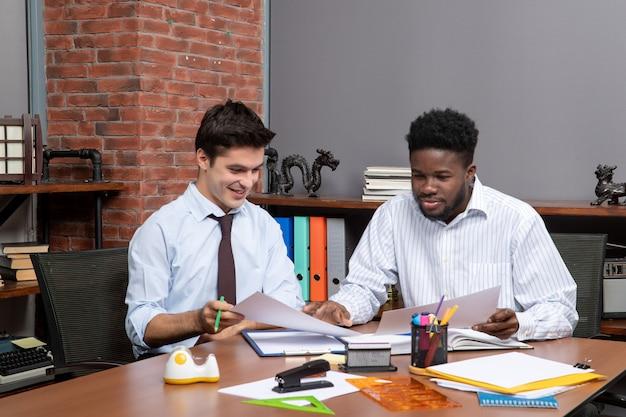 Vooraanzicht twee tevreden zakenlieden die project op kantoor bespreken