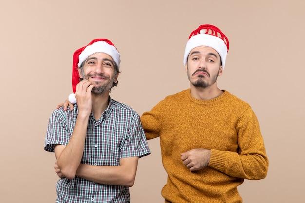Vooraanzicht twee verwarde jongens met santahoeden die zijn hand op de andere schouder op beige geïsoleerde achtergrond zetten