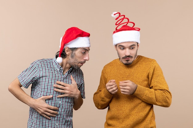 Vooraanzicht twee verwarde jongens met santahoeden één die de anderen bekijken op beige geïsoleerde achtergrond bekijken