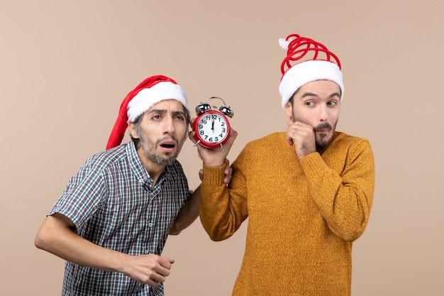 Vooraanzicht twee verwarde mannen een luisteren en de andere met een wekker op beige geïsoleerde achtergrond