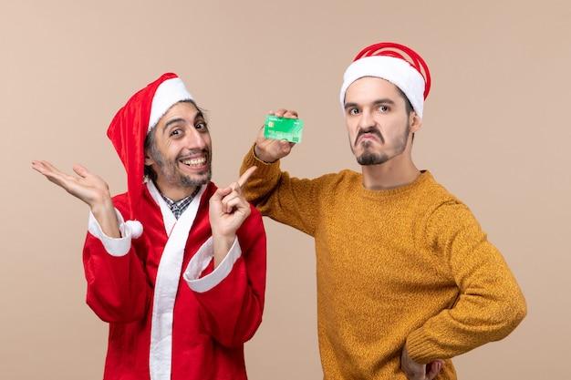 Vooraanzicht twee vrienden een met santavacht en de andere met krediet dat zijn hand op een taille op beige geïsoleerde achtergrond zet
