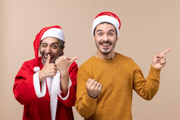 Vooraanzicht twee vrienden met santahoeden die op beige geïsoleerde achtergrond lachen