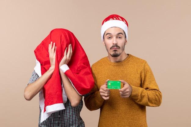 Vooraanzicht twee xmas mannen een bedrijf creditcard en de andere die zijn hoofd bedekken met santa laag op beige geïsoleerde achtergrond