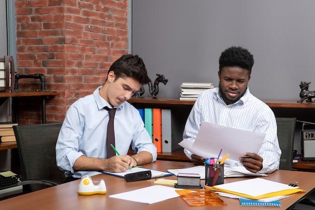 Vooraanzicht twee zakenpartners die zakelijke onderhandelingen voeren in een modern kantoor